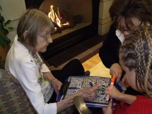 Valla and granddaughter colouring by the fire